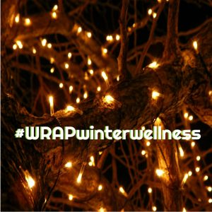 twinkle lights on a tree branch with text across that says hashtag WRAP winter wellness